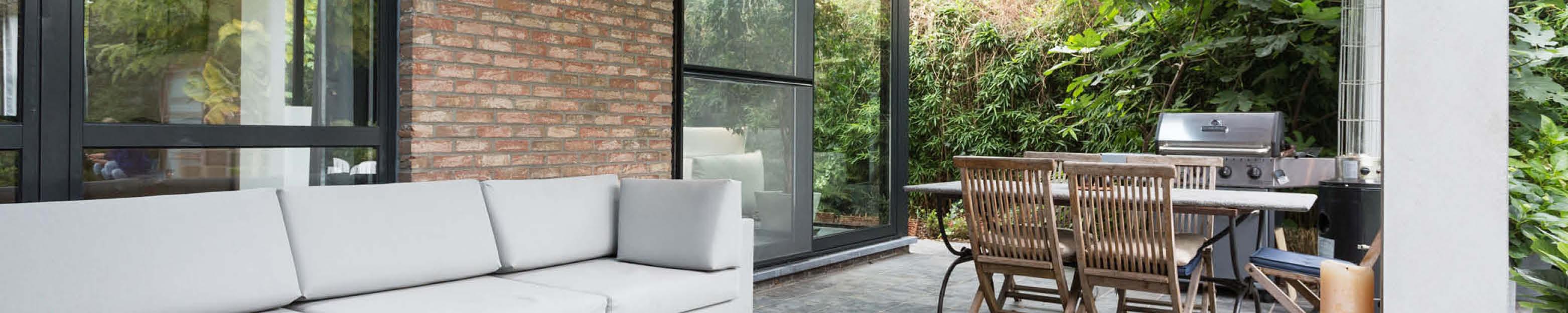 Modern leefveranda met zetel en tuintafel
